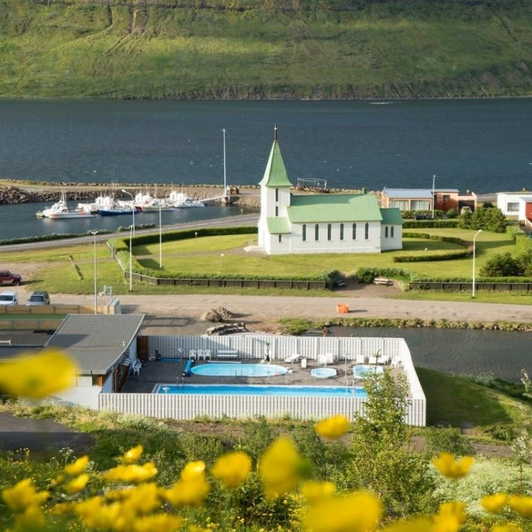 The swimming pool and the church in Suðureyri